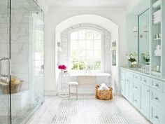 The floor with an inset basket weave of Carrara marble and black granite dots is one of the final touches that infuses Old World opulence into this master bathroom.