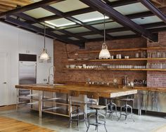 The reclaimed lumber island top is gorgeous. Love the brick walls and open shelving.