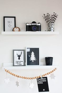 Two open shelves from Ikea display more postcards and small accessories. A jar filled with black and white straws is paired with a vintage camera, for playful accents.