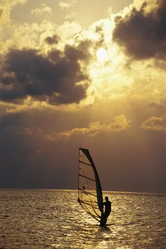 ✮ A lone wind-surfer skims the water, silhouetted by evening sun on Pamlico Sound