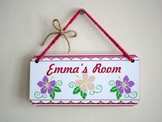 Beautifully hand finished name plaque.  Cute Children's name plaque, with Tropical flowers and striped boarder.  Plaque displays a 3 flowers in a spot pattern and a child's name, in an sweet scripted text.  Hand finished with rope hanging and a sweet little bow.  The plaque will sit proudly on any door, announcing to the world this is your little girl's room.  Perfect gift for a little one.