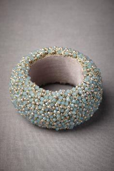 "Milky aqua Swarovski crystals and warm pearls cover St. Erasmus' fresh bangle. 3"" diameter, 1.75""W. Swarovski crystals, glass beads, acrylic pearls, brass, grosgrain ribbon. Handmade. Imported."