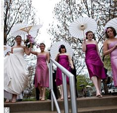 Alaynne's six bridesmaids wore strapless, silk dupioni, tea-length dresses in varying shades of pink. Alaynne gave each of her bridesmaids a white parasol to hold for their post-ceremony photo shoot. Her bridesmaids also donned pink orchids in their hair to match their dresses.