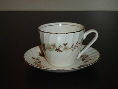 """Cup and saucerin pattern 34 by H. Aynsley  The design is a brown leaf with pale green and rust flowers on a swirled cup and saucer, gold banding on the edges and upper inside of cup  The backstamp of the saucer suggests this pattern was produced around 1946 to 1950  The cup is 2 11/16"""" (6.8 cm) high x 3 5/16"""" (8.4 cm) at the brim and the saucer is 5 11/16"""" (14.4 cm) in diameter  This set is in very good condition with little or no signs of usage  Made in England    These items have no…"""