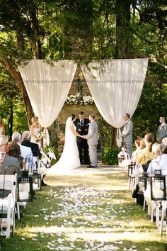 A chandelier, flowing fabric, and white flowers create a stunning backdrop for this rustic ceremony. DIY wedding ideas and tips. DIY wedding decor and flowers. Everything a DIY bride needs to have a fabulous wedding on a budget! Wedding Ceremony Ideas, Ceremony Decorations, Outdoor Ceremony, Wedding Backdrops, Outdoor Weddings, Wedding Altars, Wedding Reception, Wedding Draping, Wedding Arches