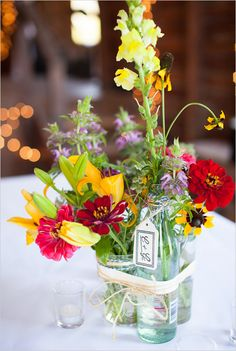 Easy way to bring together flowers on the tables that are in different types of containers. Looks like I need some raffia.