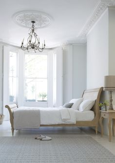 Loaf's Lauren oak sleigh bed shot with white linen underneath high ceilings and chandelier. Lovely!