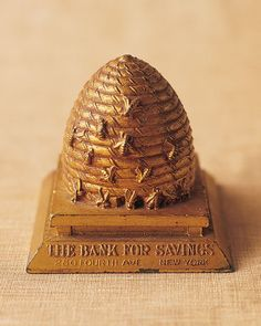 In the 1920s, local savings institutions encouraged children to be thrifty by giving them free coin banks, such as this gilded-pot-metal hive inscribed with the bank's name.