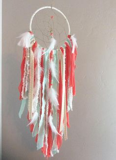 This dream catcher is made of the trendiest colors; gold, mint, and coral! This is a reddish-coral (orange-coral available upon request). A long beaded strand trails down the center, featuring white feathers, and gold ribbons. SIZE IN PHOTOS: 8x28 MATERIALS: Stainless Steel Hoop Gold