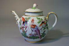 Teapot; porcelain; large dishevelled exotic birds in landscape; some gilding; flower-shaped knob on cover.