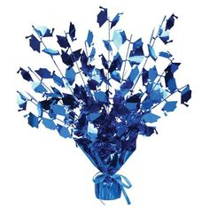 """Celebrate the new graduate  in style with our large selection of Graduation Party decorations. The Gleam N' Burst Graduation centerpiece features a blue spray centerpiece with blue metallic foil grad caps. This beautiful arrangement of blue graduation caps measures 15"""" tall and is the perfect tabletop decoration at any graduation celebration. One spray centerpiece per package."""