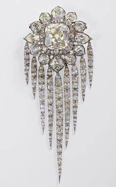 Made in 1856 by R & S Garrard, Queen Victoria's Fringe Brooch holds a large old brilliant cut diamond surrounded by twelve fancy shaped brilliants with nine diamond chains suspended below.