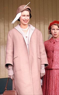 telegraph:  Queen Elizabeth in pale pink coat ensemble and dress and a feathered hat, with Princess Anne at the Highland Games, Braemar, Scotland, 1962