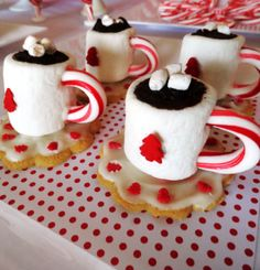 Cocoa cups made from marshmallows and candy canes with a cookie saucer