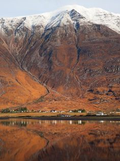 """Torridon village dwarfed by the mighty Liathach, Torridon, Wester Ross. Torridon has some of the best mountain walking in Scotland, the three Torridon """"Giants"""" Beinn Allign, Liathach, and Beinn Eighe."""