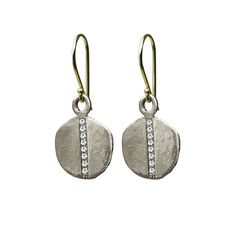 Visibly Interesting: Brushed Sterling Silver disc drop earrings with a vertical row of White Diamonds down the center of each. Discs dangle from contrasting 14k Gold ear wires.  Created by Livewell Designs known for their hip, laid-back luxe aesthetic.