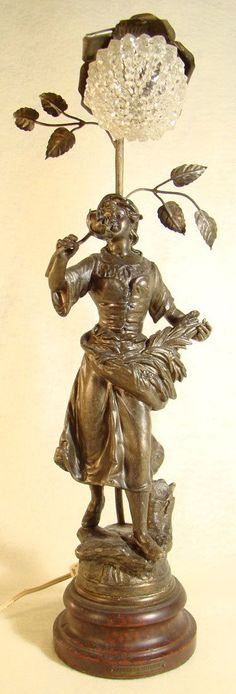This wonderful 1910 Newel post lamp is 100% original, portraying a beautiful peasant girl gathering flowers, with a rose and rose leaves on a vine supporting the light behind her. The original wood base is signed APRES LA MOISSON PAT GEO MAXIM