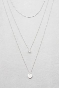 Long triple layered silver necklace with pendants.