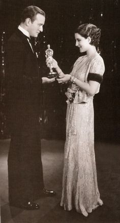 """Norma Shearer receiving her Best Actress Oscar for """"The Divorcee"""" from Conrad Nagel in 1930."""