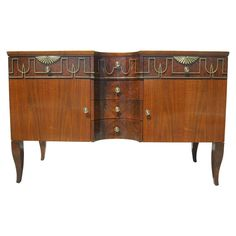 This elegant sideboard by John Widdicomb is composed of beautiful walnut veneer and walnut burl with decorative brass accents and knobs. It features four concave drawers between two spacious cabinets. Novecento Collection Sideboard by John Widdicomb |