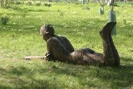 Lying Figure by Carol Peace. A life-size outdoor sculpture. 108 l x 32 w x 53 h cms Edition of 9 in bronze resin
