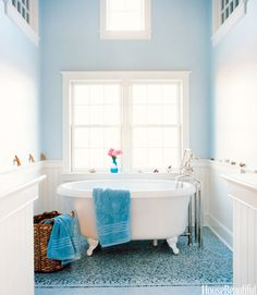 A Nantucket beach house's blue master bathroom gets its airy look from high ceilings and walls painted with Farrow & Ball's Borrowed Light. Designer Frank Roop drew the mosaic tile floor on a computer with CAD software, and Tile Showcase manufactured it in one piece, like a carpet.   - HouseBeautiful.com