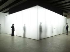 people walking around inside glass box full of fog