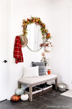 Foyer and mudroom fall decor inspiration with a mixture of neutral & colorful fall decorations for your home.   Foyer fall decor ideas for your home   Fall mudroom decor with neutral fall decor mixed with orange fall decor   Round mirror with garland   Garland hanging from mirror   Settee under a staircase   White house fall decor ideas   Easy fall home decor   Shoe basket under bench   Basket of pumpkins   Fall magnolia wreath   Fall floral stems and maple leaves   Fall throw and pumpkin pillow Hallway Decorating, Entryway Decor, Decorating Your Home, Foyer, Modern Entryway, Entryway Ideas, Decorating Tips, Autumn Inspiration, Home Decor Inspiration