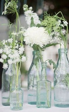 white flowers in blue and green old glass bottles - simply beautiful