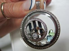 'My Story': family script, clock, meaning 'family time', ring for my husband, 3 heart birthstones for my children, & 2 pearls for my 2 grand-daughters in the *new* Legacy Living Locket w/Crystal Window Plate and *new* stripe Plate! You can order your story @ www.BeHOOTifulLocketts.OrigamiOwl.com Want to join my team, my Designer #34392, & don't forget to follow me on facebook.com/KarenBrownSchoenfeldt