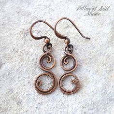 Handmade copper earrings. • Metal: solid copper. • Lightweight. • Because each pair is handmade, please expect slight differences from those shown in the photos. Solid copper wire was used to form these curly double spiral shapes. The ear wires are also solid copper. They were