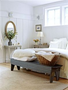Cottage bedroom...table vase & mirror bench at the end of the bed.