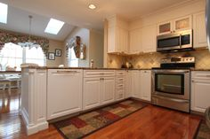 Transitional Style White Kitchen with Granite Countertops in Ellicott City, Maryland.  The dishwasher is hidden behind an appliance panel. The decorative rope corner posts combine with the raised panel cabinets and crown molding to  bring a traditional influence to the otherwise clean and contemporary lines of this room.