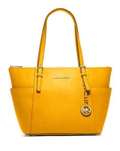 This chic East West tote from Michael Kors is wrapped in saffiano finished leather with polished hardware. The interior is lined in Kors logo fabric and features a zippered pocket, four open slip pockets, and a key fob. It has a fully zippered top closure, and there are side gusset pockets for additional storage. The front is accented with Michael Kors lettered logo and a removable Kors circular logo hang charm. Four metal 'feet' help protect the bottom of your bag. Dual leather straps have…