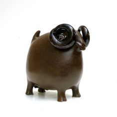 A new medium sized Billy Goat glazed in a bronze color with dark shiny brown black horns.  His horns curl round and round, he looks like a wild