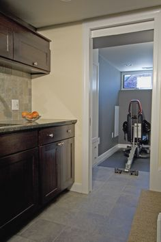 This #basement entertainment area with #kitchenette transitions smoothly into an exercise room.