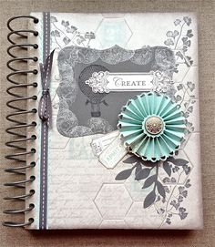 Petite Fleur Paperie. The artist used a combination of many elements without making the journal look overdone. The subtle colors of Basic Gray, Basic Black, White, Crumb cake, and blue work well. The rosette and Basic Gray Ribbon add dimension. I like the choice of the Top Note die cut.  The subtle En Francais, and postage Due stamp sets work great. The honeycomb shows through, but doesn't restrict the artwork.