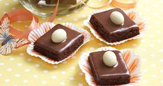 These choc-coconut slices are smothered in rich ganache and topped with a white chocolate egg for an Easter twist.