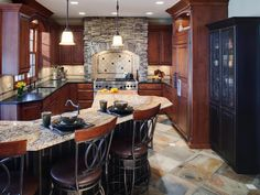 This traditional kitchen features bar seating, rich wooden cabinetry and pendant light fixtures. A stone-and-tile backsplash brings in an Old World feel.