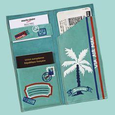 une pochette en cuir bleu turquoise peinte de motifs de voyage bleu, blanc et rouge, faite pour ranger ses papiers, son passeport et ses billets de transport en vacances.