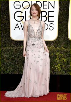 Emma Stone in a Valentino couture gown, Jimmy Choo shoes, Tiffany and Co jewelry, and Valentino clutch.