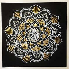 mandala design with white ink and metallic sharpie on black paper.