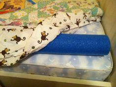 Pool noodle under fitted sheet: solution to keep a toddler in the toddler bed.   smart!