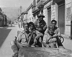 A group of 28 (Maori) Battalion soldiers drive along a street in Sora, June 1944.