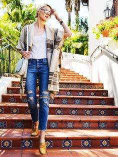 Fashionata in a wool poncho, white tee, distressed jeans, and tan leather loafers.