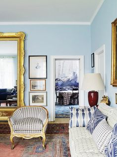 Pale blue living space with patterned white and blue pillows on sofa // Italian design