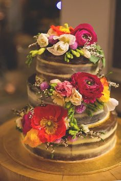 Naked wedding cake decorated with bright flowers | Jenna Fahey-White | See more: http://theweddingplaybook.com/colourful-vintage-diy-wedding/