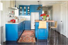 """Color is BM Caribbean Azure 2059-20. Cabinets are a """"modern take on Shaker style""""; the rails are 3"""" instead of the traditional 2 1/4"""". White tiles in a grid to bounce light around.  Induction stovetop on left with microwave/convection oven in island.  The other side of the fridge is a bookcase.  1' deep pantry/storage on other side of the island.  Colorado Mountain Retreat"""
