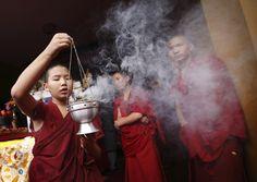 Monk blows on incense during 77th birthday celebration of exiled spiritual leader Dalai Lama in Kathmandu