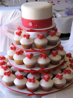 Sweet combo - small wedding cake layer on top, surrounding red cupcakes on bottom.